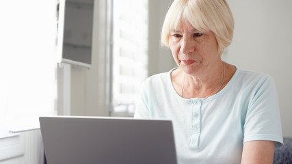 Elderly senior blond woman working on laptop computer at home. Remote freelance work on retirement, active modern lifestyle of older people.