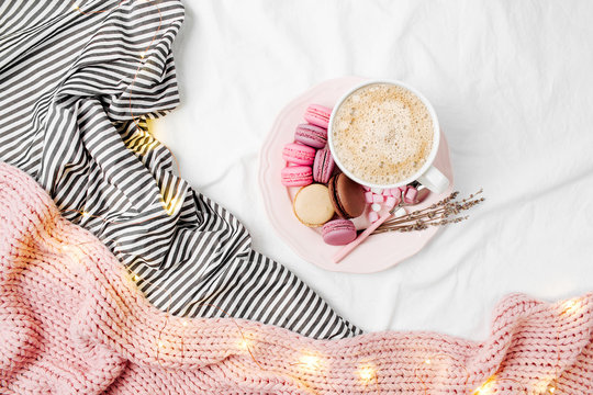 Cup of coffee and macaroons on bedding with fairy lights. Copy space. Flat lay, top view