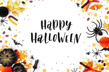 Halloween holiday background with colorful candy, bats, spiders, pumpkins and decorations. Flat lay. View from above