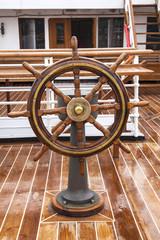 timón de madera situado en la cubierta de madrea en un barco de pasajeros