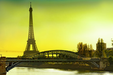 View of the Eiffel tower and Cygnes bridge over Seine river at sunrise, Paris