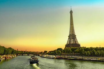 Touris and cargo boats sail on Seine river with view of Eiffel tower a Paris landmark at sunrise