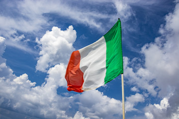 Italian flag waving in the blue sky