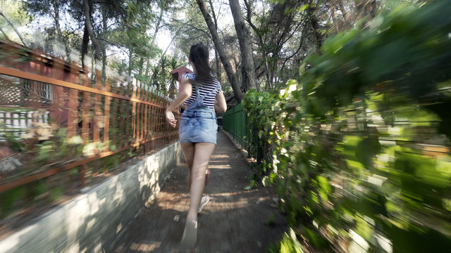 Tracking two girls are running away fast in narrow passage path in forest houses neighbourhood