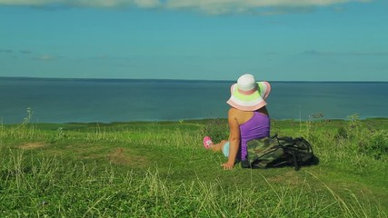 deab4bb11ef17 0 08 a woman in a straw hat and a nearby backpack sitting on a mountain and  admiring