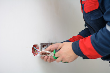 Electrician hands tighten electrical wires in wall fixture or socket using a screw driver - closeup. Installing electrical outlet or socket - closeup on electrician hands