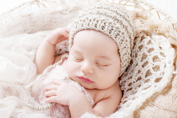 Sweet newborn baby sleeping.  Newborn boy 3 weeks old lying in a basket with knitted plaid. Portrait of pretty  newborn boy. Closeup image