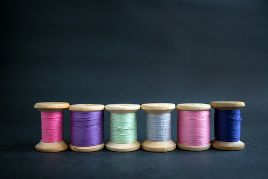 Set of pastel colors thread for sewing on a black background. Set of threads on bobbins retro style. Vintage accessories for sewing on the table. Multicolor spools of thread isolated