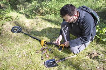 Fototapeta Mężczyzna trzyma w dłoni znaleziony w ziemi przedmiot. Wykrywacz metalu i saperka leżą obok niego. obraz