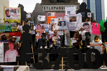 Relatives hold pictures of missing persons during a demonstration to mark International Day of the Victims of Enforced Disappearances in Mexico City