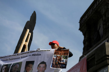 A relative holds a picture of a missing person during a demonstration to mark International Day of the Victims of Enforced Disappearances in Mexico City