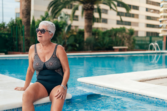 Senior old woman grey hair sitting by the swimming pool