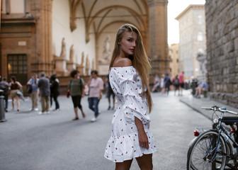 A beautiful girl in a light sundress strolls through an ancient city  Wall mural