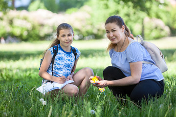 Mom helps girl while drawing in nature, teaches her daughter, holds pencils. Looking at camera