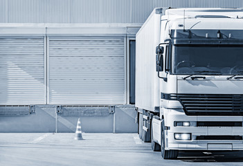 Freight truck stands by the door of the storage.
