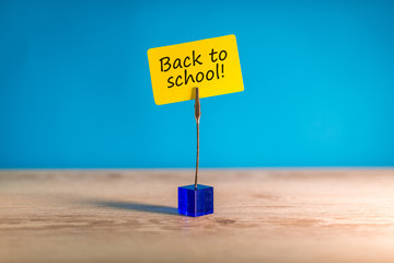 Back to school - Inscription on little yellow tag at blue background. 1st september concept