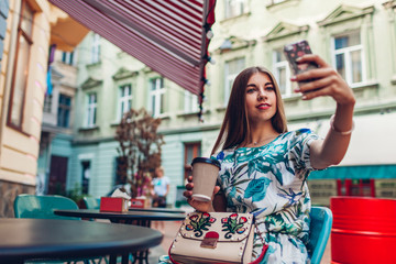 Outdoor portrait young beautiful woman taking selfie using phone. Girl drinking coffee in Lviv cafe.