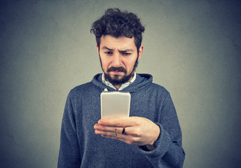 Angry annoyed man using smartphone