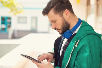 Handsome man with headphones using tablet