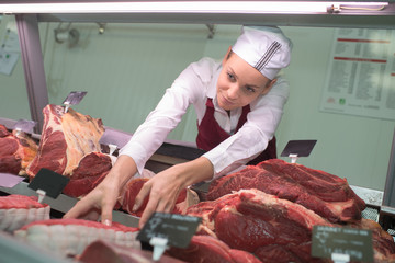 high angle view of female butcher picking meat in butchery