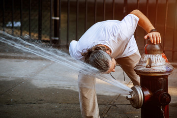 Man is refreshing himself in Public square summer high temperature with Fire hydrant water