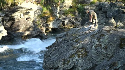 Wall Mural - Caucasian Hiker on the Large Boulder. Rocky River Gorge. Norway, Europe.