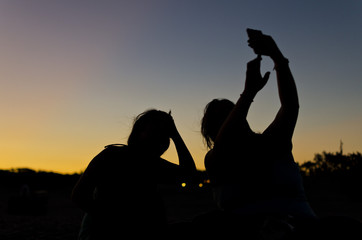 silhouette of two people taking a picture at dusk