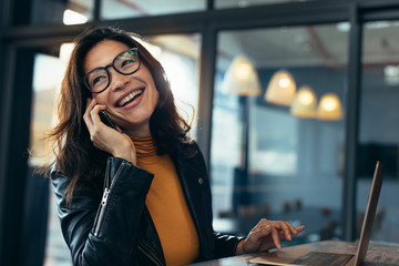 Smiling business woman in casuals talking on phone Wall mural
