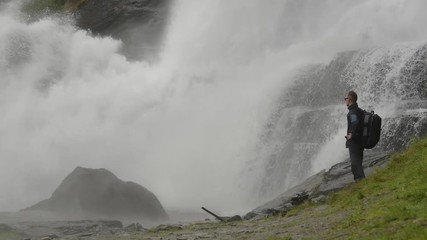 Wall Mural - Caucasian Traveler with Backpack on the Edge of the Waterfall. Slow Motion Footage