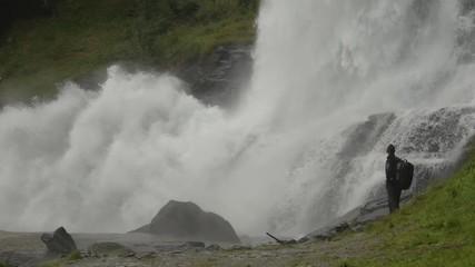 Wall Mural - Hiker Enjoying the Scenic Waterfall Vista. Norway, Europe. Slow Motion Footage