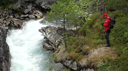 Wall Mural - Hiker on the Rocky Mountain River Shore in Slow Motion