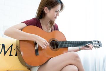 Young beautiful Asian woman sitting on sofa playing guitar - girl music, having fun concept.