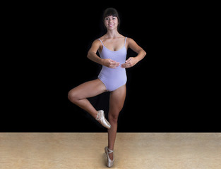 Ballerina wearing a lilac leotard in studio and black background
