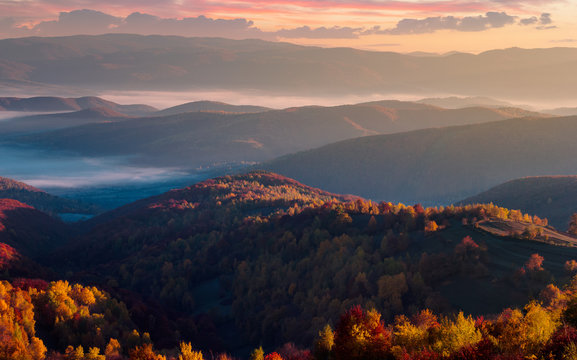 gorgeous red sunrise in mountains. forested hills in colorful fall foliage. fog in the distant valley