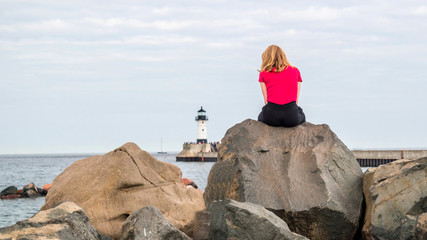 A young girl with blonde hair and red shirt is sitting on a rock to look at lighthouse on Lake Superior
