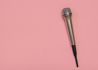 Retro microphone with wire on pink background. Minimalism.. Flat lay.
