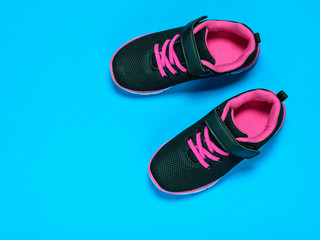 Black with red children's sneakers on a pink background.
