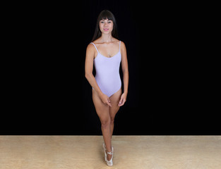Ballerina wearing a lilac leotard standing on toes on a black background