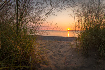 Scenic Sunrise Beach. Summer sunrise framed by dune grass and sandy beach path to the clear waters of Lake Huron. Port Huron, Michigan.