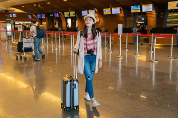 asian visitor walking in the hall. carrying luggage in airport.
