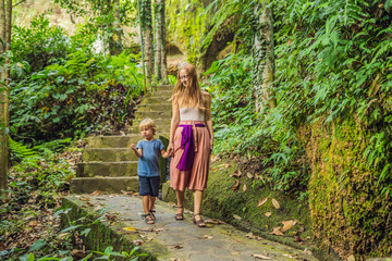Mom and son on background of Gunung Kawi. Ancient carved in the stone temple with royal tombs. Bali, Indonesia. Traveling with children concept