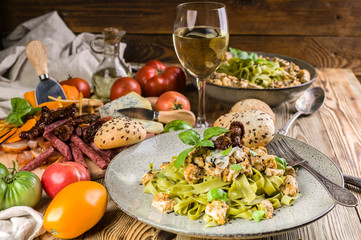 Pesto pasta with meat on a plate, a variety of cheeses and smoked meat and sausage, a glass of white wine, vegetables and spicy herbs on a wooden table. Close-up
