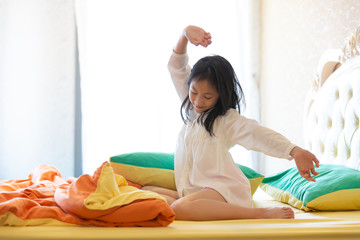 Beautiful girl waking up in her bed,Asian girl smiling and stretching,healthy lifestyle,wellness concept