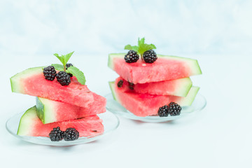 Watermelon sliced pie with blackberries and mint leaf on blue pastel background.