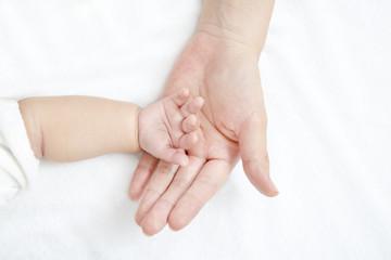 新生児の小さな手包むように乗せたお母さんの大きな手、愛情、母性イメージ
