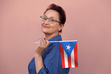 Puerto Rico flag. Woman holding Puerto Rico flag. Nice portrait of middle aged lady 40 50 years old with a national flag over pink wall background outdoors.