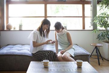 ソファーに座ってスマホを操作する女性社員たち