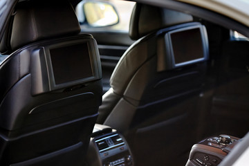 Car inside. Interior of prestige luxury modern car. Two displays for back seats passenger with media control panel copy space mock up