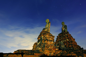 Buddha Statue and Ancient Temple at night with cloud sky and stars on Wat Chaiwatthanaram at Ayutthaya, Thailand
