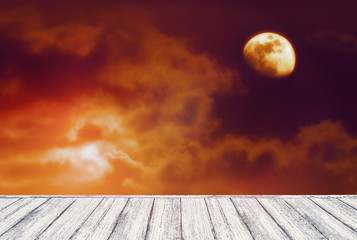 Background of dark night sky with mysterious clouds, red moon eclipse and table in shabby chic style. Moon is taken by me with my camera.